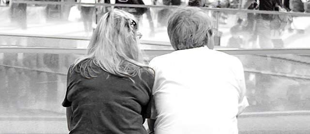噴水前のベンチに座り、寄り添い話をする年配の男女の後ろ姿