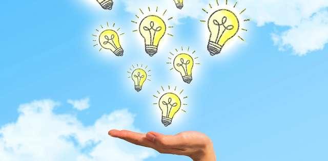 青空を背景に、手のひらを上に向けて、その上に黄色い電球のイラストがたくさん浮かんでいる画像