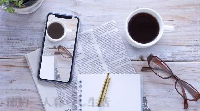 白っぽい木目調のテーブルに置かれたスマホ、コーヒー、新聞やノート、ペンにメガネが置かれている