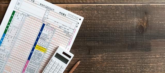 木目のテーブルの上に確定申告の申告書Bと電卓とえんぴつが置かれている
