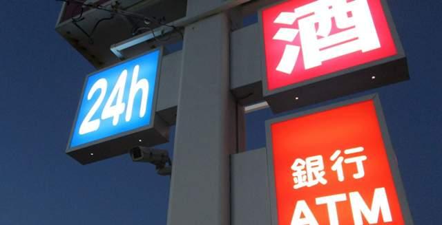 夜のコンビニの24h、酒、銀行ATMと書かれた看板
