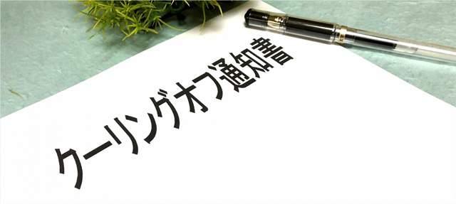 クーリングオフと書かれた白い紙とペンがテーブルに置かれ、かたわらに植物が置かれている
