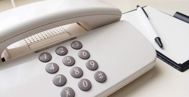 机の上に置かれた固定電話とメモとペン