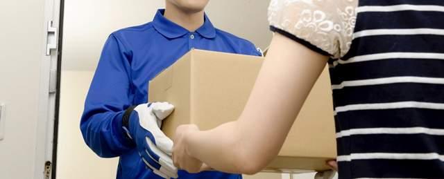 玄関で荷物の受け渡しをする宅配業者と住人の女性