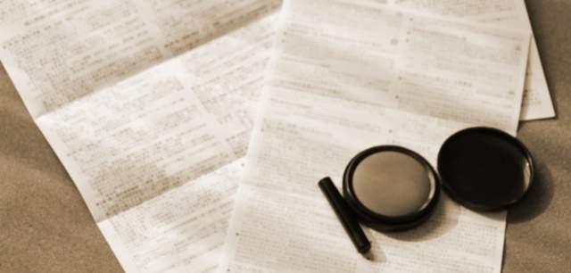 契約書とハンコと朱肉がテーブルに置かれているセピア色の画像