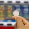 自動販売機を前に100円玉をつまんで掲げる右手