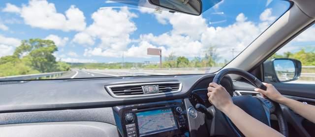 晴天のもと運転する人の手とフロント方面の画像