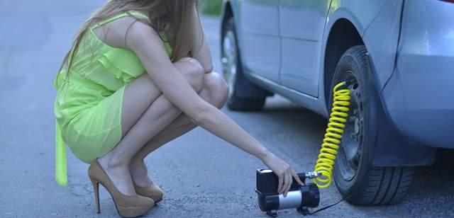 後ろタイヤにしゃがんで空気を入れる黄緑色のワンピースを着た外国の女性