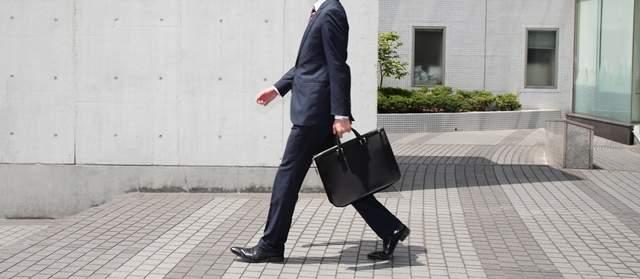 コンクリートの建物の敷地を歩く、ビジネスバッグを持ったスーツ姿の男子
