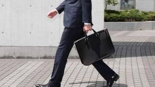 ビジネス鞄を持って歩くスーツの男性