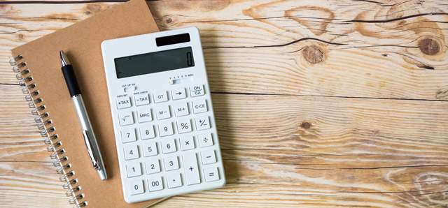 木目調のテーブルの上に、ノートと電卓とペンが置かれている