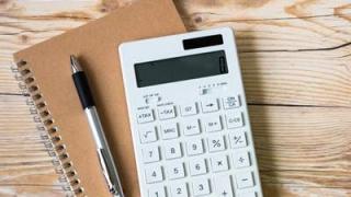 机の上にノートと電卓とペン