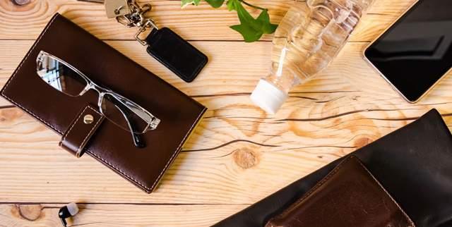 財布、車の鍵、メガネ、ペットボトルの水などが木の机に無造作に置かれている