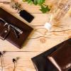 木の机の上に財布や鍵など身の回り品が置かれている