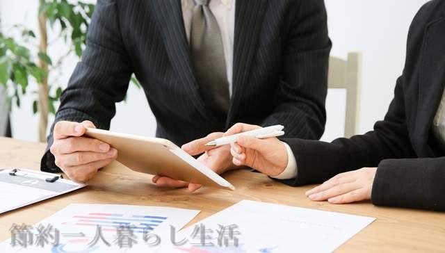 テーブルにつきタブレットを見ながら打ち合わせするスーツ姿の男女の首からしたの画像