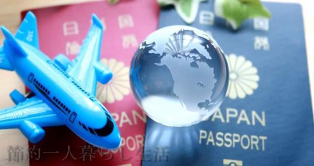 赤と青2冊のパスポートの上にガラスの地球をかたどった玉と飛行機の模型