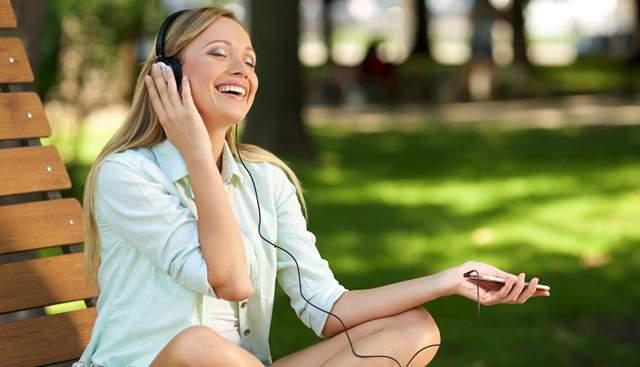公園のベンチに座りスマホにつながったヘッドフォンを付けて、笑顔で音楽に酔いしれる外国の女性