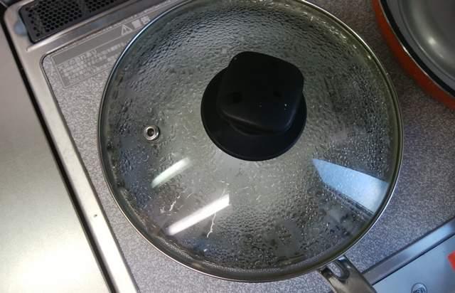 鍋に沸かしたお湯にお米を入れてフタをして煮ている様子
