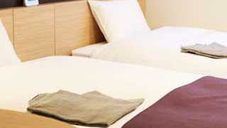ホテルのツインベッドに白い布団、枕に小豆色のカバーでおしゃれな小さい画像