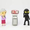 ATMを挟んで電話する、年配女性と悪人の人形