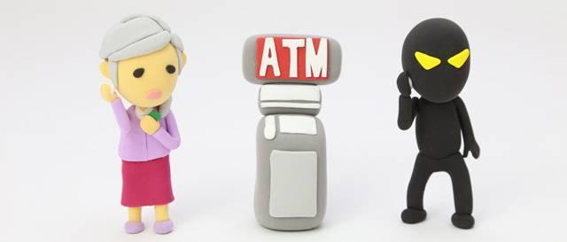 おばあさんと悪い人っぽい人形が、ATMの模型を挟んで並んでいる