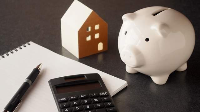 黒い光沢がある机の上に、家の模型、ノート、ペン、電卓、ブタの貯金箱が無造作に置かれている