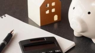 ブタの貯金箱と電卓とノート