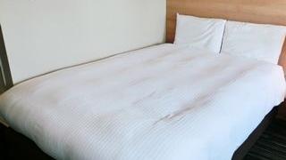 ビジネスホテルの部屋のベッドに白い布団と枕2個が置かれた小さい画像