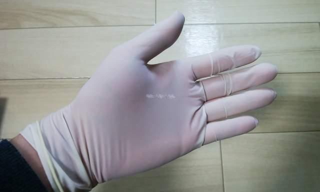 ピッタリタイプのビニール手袋を手にはめた様子